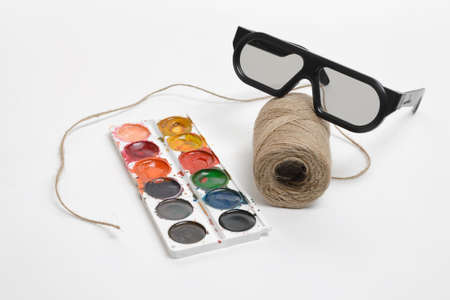 tempera: Top view of art scene featuring of thread twine, glasses and watercolor paints on a white background. Equipment of art designer. Stock Photo