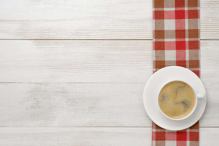 vivacity: Workplace with cup of coffee on red checkered kitchen tablecloths on wooden surface in top view. Vivacity in the mornings. Keeping healthy. Coffee breakfast. Increase working efficiency.