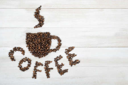 fragrant: Coffee beans making a word coffee and shape of cup of fragrant hot coffee on wooden background