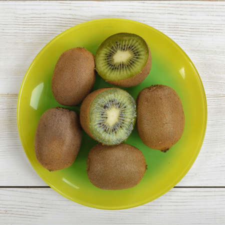 enzymes: Halves and whole kiwi placed on a plate. Top view. Helping digestion with enzymes. Boosting immunity. Creating alkaline balance. Naturally organic food. Premier Antioxidant Protection.