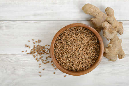 gallstones: Pearl barley in a pot and ginger on wooden surface in top view. Natural remedy. Weight loss. Helping prevent gallstones. Improves skin elasticity. Improving heart disease risk factors. Treating chronic indigestion. Reducing cholesterol levels. Reducing mu