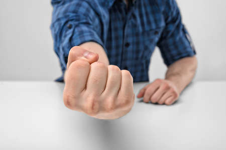 Close-up de hand van de mens toont gebalde vuist. Lichaamstaal. Handgebaar. Agressie en bedreiging. Defensieve reactie.