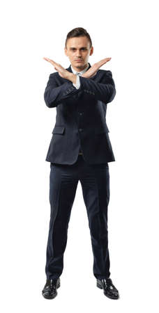 prohibitions: Serious businessman making X sign with his arms to stop doing something. Signs symbols. Body language. Prohibitions and restrictions. Front view. Office clothes. Dress code. Stock Photo