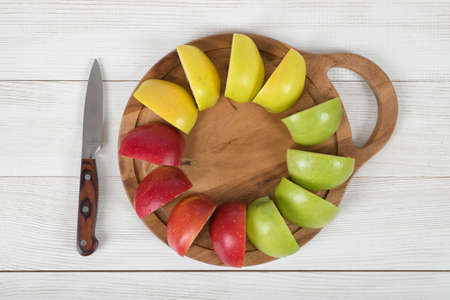 source of iron: Composition of apple pieces on wooden cutting board and a knife next to it in top view. Healthy food. Boosting immune system. Table setting. Improving health. Food decoration. Natural source of iron for anemia. Stock Photo