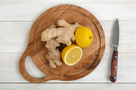 indigestion: Lemon halves and ginger laid out on a wooden cutting board . Top view. Ingredients to take for colds. Boosting immune system. Natural remedy. Instant relief from nausea and indigestion. Weight loss.