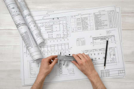 architect drawing: Hands of architect holding a centimeter device over drawing layout in top view. Workplace of architect or constructor.. Engineering work. Construction and architecture. Architect drawing. Measurement. Stock Photo