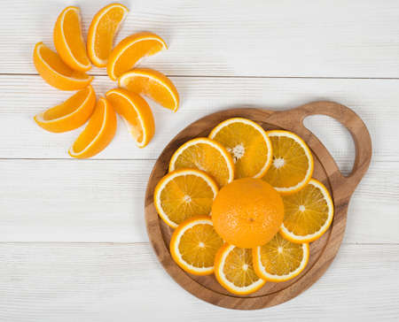 ageing: Orange slices are well decorated on a cutting board. Top view composition. Food decoration. Boosting immune system. Helps prevent ageing of skin. Protects your vision. Stock Photo