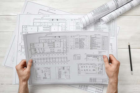 architect drawing: Hands of architect holding a drawing sketch. Workplace of architect. Engineering work. Construction and architecture. Architect drawing. Project.