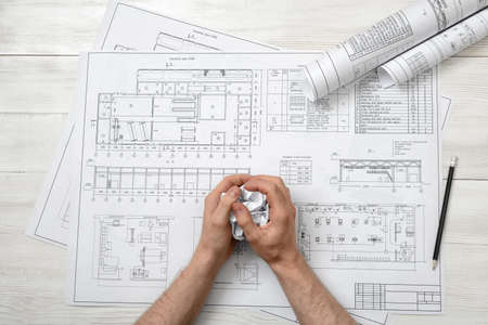 masculine: Closeup masculine hand with hand-folding a piece of paper. Top view composition. Anger sign. Worry process. Workplace of architect or constructor. Engineering work. Construction and architecture. Architect drawing. Draft. Stock Photo