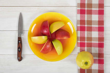 source of iron: Composition of apple pieces on plate and a knife next to it in top view. Healthy food. Boosting immune system. Table setting. Improving health. Food decoration. Natural source of iron for anemia.