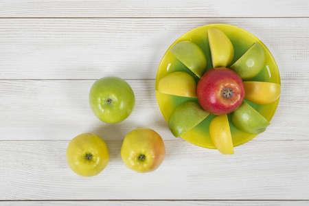source of iron: Top view of juicy yellow and green apples placed around the whole apple on a saucer. Table decoration. Healthy food. Improving health. Beating diarrhea and constipation. Boosting immune system. Natural source of iron for anemia. Stock Photo