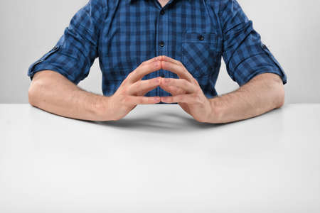 clasped hand: Cropped portrait of a man sitting with his clasped fingers. Readiness to talk. Symbols and gestures. Body language. Hand gesture. Readiness for work. Listen attentively. Straight posture.
