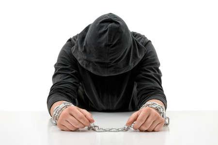 Hombre con las manos en las cadenas está sentado con la cabeza inclinada. Crimen y castigo. Infracción de las leyes. La culpa y remordimientos. Delincuente en cautiverio. Restricción de la libertad. Foto de archivo - 58429319
