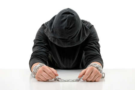 head bowed: Man with hands in chains is sitting head bowed. Crime and punishment. Offense against the law. Guilt and remorse. Offender in captivity. Restraint of liberty.
