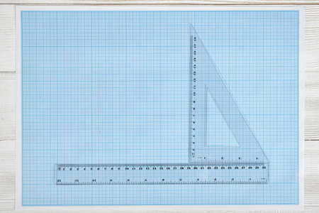architectural drawing: Triangle centimeter ruler and simple centimeter ruler on a blueprint. Top view composition. Measuring process. Work place of draftsman, architect, constructor. Engineering work. Construction and architecture. Architect drawing. Measurement. Stock Photo