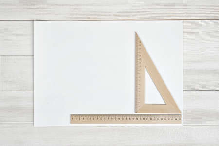 construction draftsman: White paper with triangle centimeter ruler and simple centimeter ruler. Top view composition. Measuring process. Work place of draftsman, architect, constructor. Engineering work. Construction and architecture. Architect drawing. Measurement. New project. Stock Photo