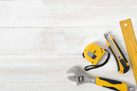 space for type: Construction tools including centimeter ruler, wrench and cutter placed in the right down corner on wooden surface with open space. Top view composition. Measurement. Fixing and cropping. Hand tool. Tools for carpentry work. Type of fastener. Mend and rep