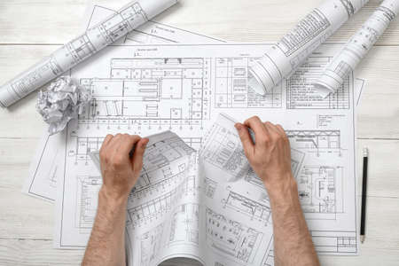 architect drawing: Close-up hands of architect tearing a bad architect drawing. Anger sign. Worry process. Nervous condition. Workplace of architect or constructor. Engineering work. Construction and architecture. Architect drawing. Draft. Stock Photo