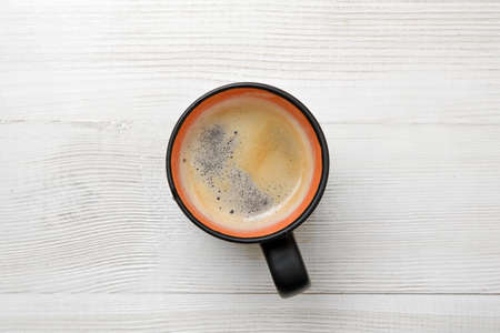 overtime: Cup of hot coffee on a wooden surface. Top view. Workplace of office man. Willingness to work overtime. Increasing productivity in the mornings. Improving mood and productivity. Coffee breakfast.