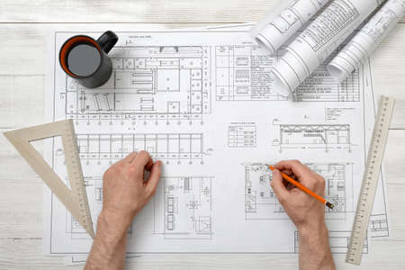 architect drawing: Close-up hands of architect working with pencil on a drawing. Workplace of architect. Engineering work. Construction and architecture. Architect drawing. Non-stop work.