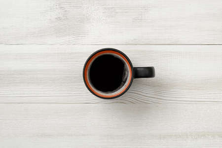 cheerfulness: Cup of hot coffee on a wooden surface. Top view. Workplace of office man. Willingness to work overtime.  Increasing productivity in the mornings. Improving mood and productivity. Coffee breakfast.