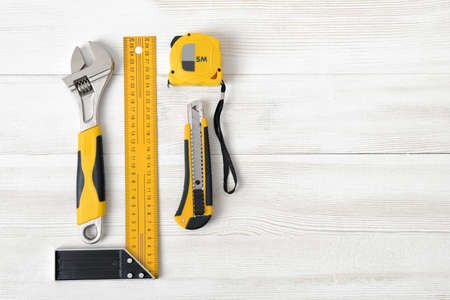 fastener: Building tools including centimeter ruler, wrench and cutter placed in the right side on wooden surface with open space. Top view composition. Measurement. Fixing and cropping. Hand tool. Tools for carpentry work. Type of fastener. Mend and repair. Parts