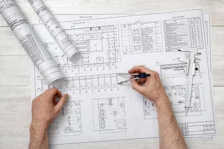 man measurement: Close-up hands of man holding an engineering divider over drawing plan in top view.  Workplace of architect or constructor. Engineering work. Construction and architecture. Architect drawing. Measurement. Draftsmanship. Stock Photo