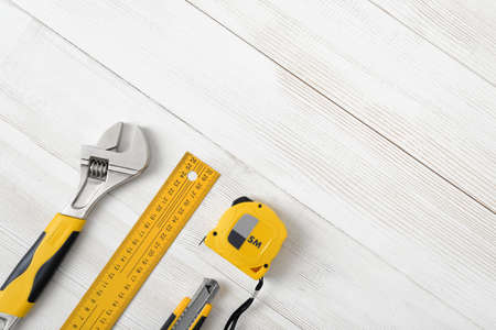 fastener: Construction tools including centimeter ruler, wrench and cutter placed in the right down corner on wooden surface with open space. Top view composition. Measurement. Fixing and cropping. Hand tool. Tools for carpentry work. Type of fastener. Mend and rep
