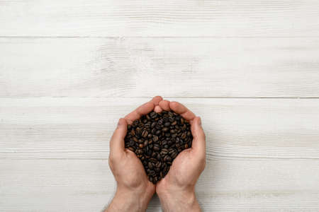 uplifting: Close-up hands of man holding a handful of coffee beans. Top view composition. Workplace coffee maker. Top view. Coffee house. Uplifting mood. Coffee break.