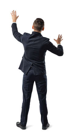 dress code: Back view of businessman touching big sensor panel or wall. Obstacles and barriers. Office clothes. Dress code. Confusion and doubt. Search exit. Pantomime.