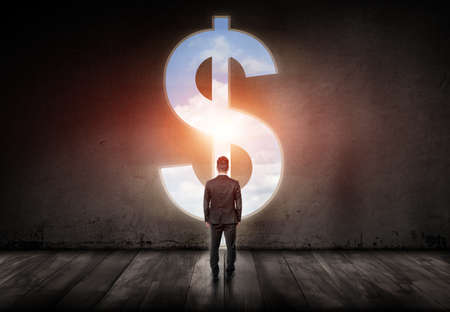 power of money: Well-dressed man standing in a big room in front of big silver dollar sign with blue sky inside it. Symbol of power, money and freedom. Targeting success and happiness. Back view.