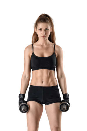 Cutout fitness model wearing sportswear stands looking directly at the camera, holding dumbells. Studio portrait. Healthy lifestyle. Fitness and sport. Power of body. Sportswear for training.