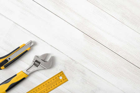 mend: Construction tools including centimeter ruler, wrench and cutter placed in the right down corner on wooden surface with open space. Top view composition. Measurement. Fixing and cropping. Hand tool. Tools for carpentry work. Type of fastener. Mend and rep