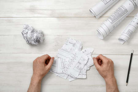 teared: Man hands on wooden table with teared designs and pen. Process of drawing. Failure. Workplace of architect or constructor. Engineering work. Construction and architecture.