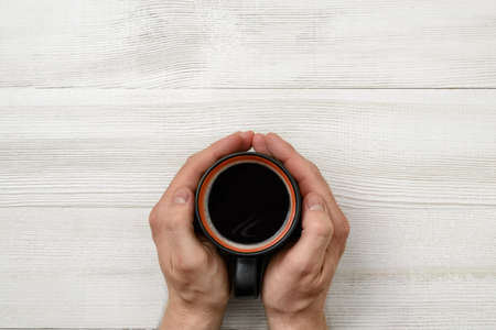 stimulant: Close-up hands of man holding a cup of coffee. Top view. Workplace of office man. Coffee house. Uplifting mood. Coffee break. Relax. Willingness to work overtime. Conducive working environment. Increasing productivity in the mornings. Improving mood and p
