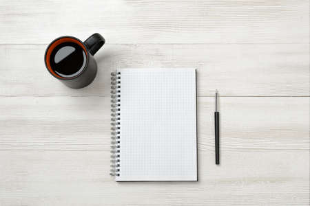 authorship: Notebook, cup of coffe and pencil put on table. Tools of writing. Studing and authorship. Marketing plan. Business planning.