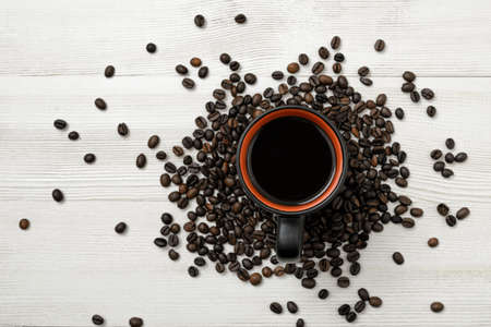 spreaded: Cup of hot coffee on a wooden surface with spreaded coffee beans. Top view. Workplace. Willingness to work overtime. Increasing productivity in the mornings. Improving mood and productivity. Art composition. Concept.