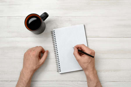 writing activity: Hands of man writing with a pencil in notebook and cup of coffee standing on wooden table. Business. Science. Study. Intellectual activity.