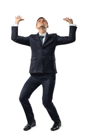 dress code: Full length of cut-out businessman pushing invisible wall under pressure. Conceptual photo. Problems and issues. Business staff. Office clothes. Dress code. Presentable appearance. Stock Photo
