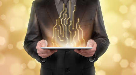 thriving: Businessman standing on blurry yellow background presenting new technologies of line diagram. New future. Thriving society. Digital presentation. Business staff. Digital tablet. Business concept. Stock Photo