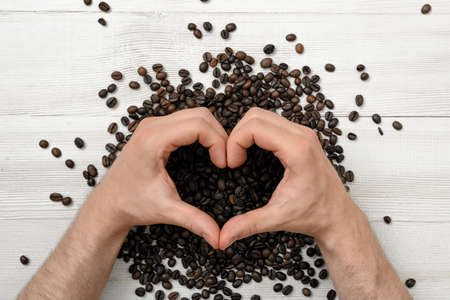 scattered in heart shaped: Close-up hands of man making shape of heart with his hands. Concept of love with coffee. Art composition. Top view composition. Workplace coffee maker. Uplifting mood.