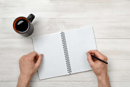 decorate notebook: Close-up hands of man holding a pen over empty notebook with cup of coffee next to it. Top view composition. Workplace of office man. First work day. Increasing productivity in the mornings. Improving mood and productivity. Stock Photo
