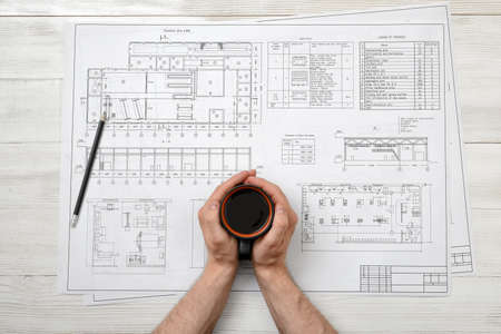 architect drawing: Close-up hands of man holding a cup of coffee over drawing layout in top view. Workplace of architect or constructor. Engineering work. Architect drawing. Uplifting mood. Coffee break. Conducive working environment. Increasing productivity in the mornings