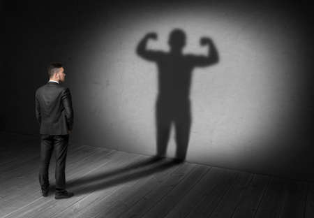 back to the future: Back view of businessman looks to his shadow with strong his display in future. Believe in yourself. Success and development. Setting and achieving goals. The look into the future.