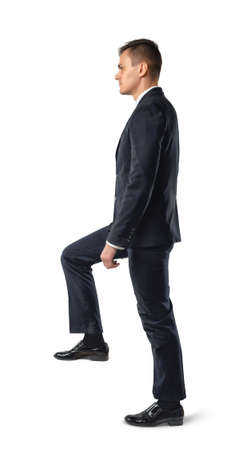 dress code: Side view of businessman climbing stairs , isolated on white background. Business staff. Office clothes. Dress code. Presentable appearance. Self-confidence. Stock Photo