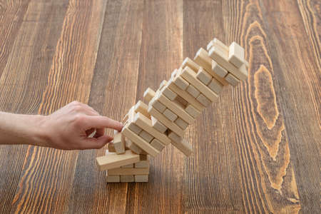 mental activity: Hands of man pushed the brick and destroyed the tower. Close-up photo. Imbalance. Collapse and destruction. Mistake. Entertainment activity. Game of physical and mental skill. Removing blocks from a tower. Stock Photo