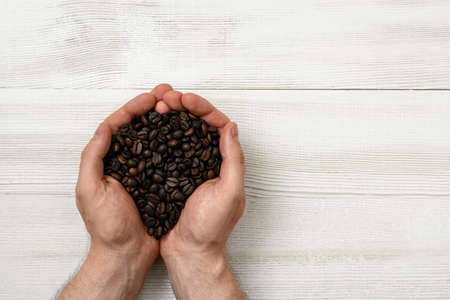 uplifting: Close-up hands of man holding a handful of coffee beans with copy space. Top view composition. Grain selection. Workplace coffee maker. Coffee house. Uplifting mood. Coffee break.