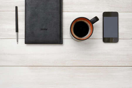 conductive: Top view of black notebook and pen with cup of hot coffee with copy space. Workplace of office man. Readiness for the new. First work day. Office stuff. Willingness to work overtime. Conductive working environment. Increasing productivity in the mornings.