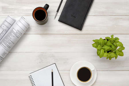mornings: Workplace of architect or contractor with office stuff and double dose of coffee. Increasing productivity in the mornings. Long and continuous operation. Willingness to work overtime. Improving mood and productivity. Workplace of office man. Top view. Stock Photo