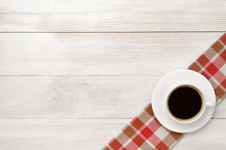 mornings: Office workplace with cup of coffee on checkered tablecloth. Top view composition. Improving mood and productivity. Increasing productivity in the mornings. Willingness to work overtime. Keeping healthy. Contribution to wellbeing. Reducing stress. Workpla Stock Photo